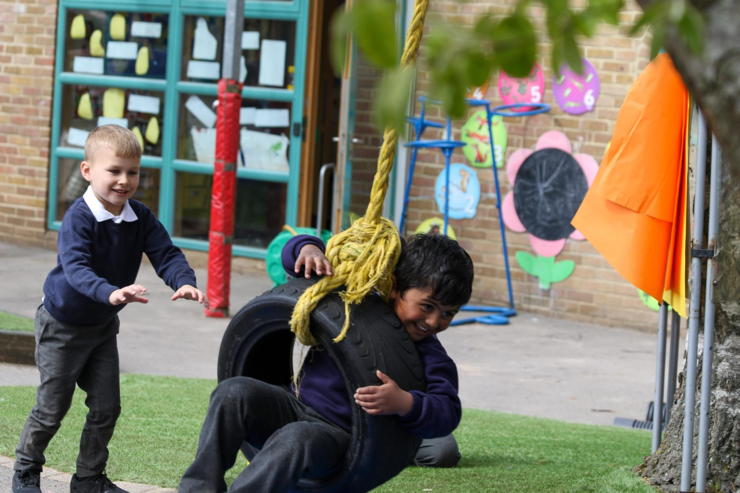 Two students playing on a rope swing